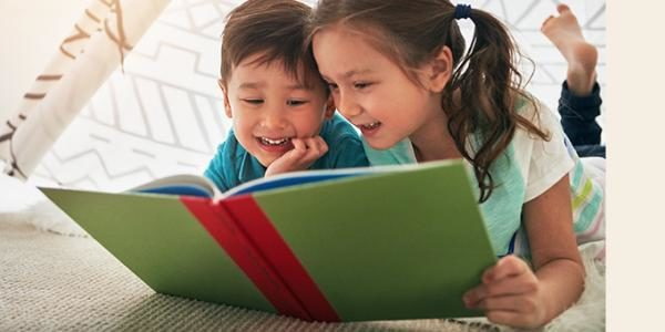 Photo of two children reading a book