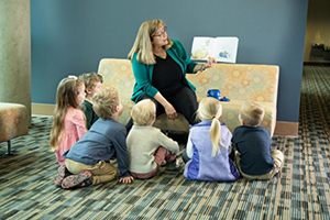 Photo of teacher reading a book to young students